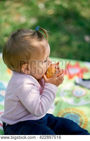 Little Girl Sits On A Blanket And Bites An Apple. Close-up. Side View