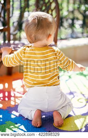 Small Child Is Kneeling On A Colored Rug On The Balcony. Back View