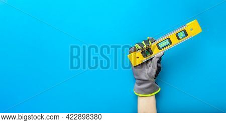 Building Level. Hand In Gloves Holds A Yellow Building Level On A Blue Background. Postcard Or Poste