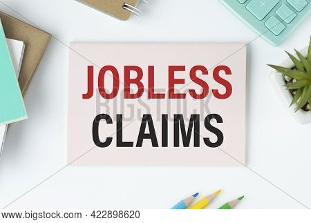 Male Hand Writing Jobless Claims On White Note, Isolated On Blue Background. Business Concept.