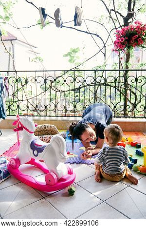 Mom Sits On The Balcony, Bending Over Near The Little Girl On The Background Of Toys