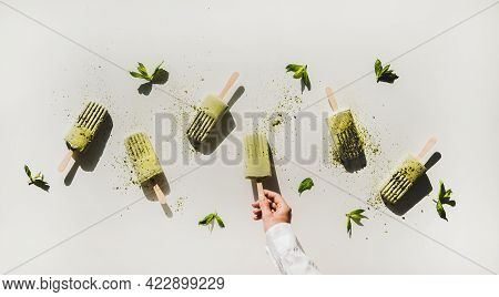 Womans Hand Taking Green Matcha Popsicle With Mint From Table