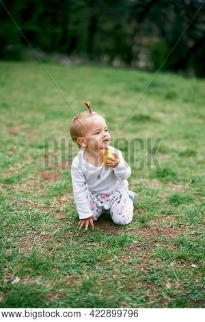 Little Girl Kneels On A Green Meadow With An Apple In Her Hand