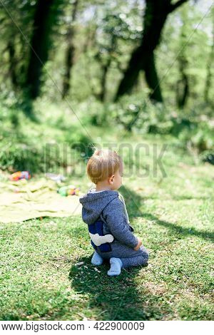 Little Girl In Overalls Kneels On A Green Lawn. Side View