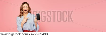 Excited Woman Holding Cellphone With Blank Screen And Pointing With Finger Isolated On Pink, Banner.