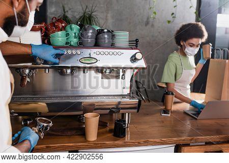 African American Barista In Medical Mask And Latex Gloves Using Coffee Machine Near Blurred Colleagu