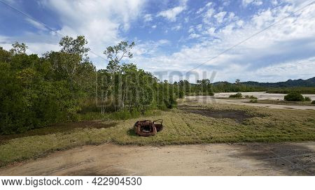 Drone Aerial Of Rusting Illegally Dumped Car Wreck On Tidal Salt Pans Beside Trees