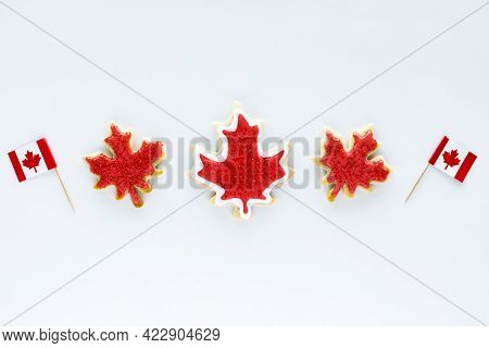 A Row Of Canada Flag Sugar Cookies With Two Mini Canada Flag Picks Isolated Against A White Backgrou