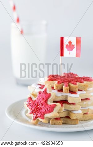 Close Up Of A Stack Of Canada Flag Cookies With A Canada Flag At The Top And A Glass Of Milk In Behi