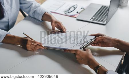 Businesswoman Holding Resume And Talking To Female Candidate, During Corporate Meeting Or Job Interv