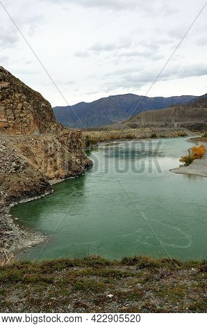 A Winding Bed Of A Beautiful Turquoise River Flowing At The Foot Of A High Mountain In A Picturesque