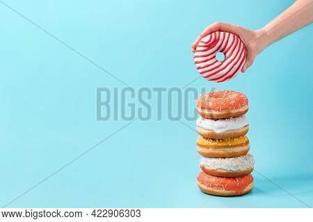 Stack Of Assorted Donuts And One Donut In Female Hand On Blue Background. Many Colorful Glazed Dough
