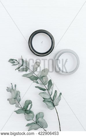 Scented Candle In Glass Jar With Natural Ingredients On White Wooden Background With Branches Of Euc
