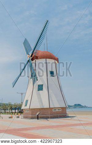 Seochon, South Korea; June 2, 2021: Windmill At Chunjangdae Beach On Sunny Day With Hazy Blue Sky In