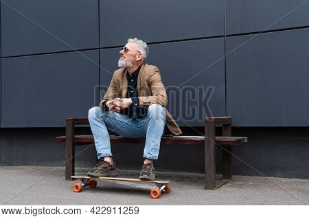 Full Length Of Middle Aged Man In Sunglasses Sitting On Bench Near Longboard Outside