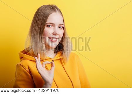 Portrait Young Woman Shows Ok Hand Gesture. Teenage Blonde Calm Smiling Girl Shows Positive Ok Gestu