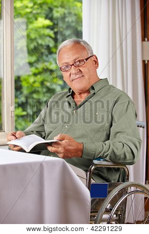 Senior man in wheelchair reading a book in a rest home
