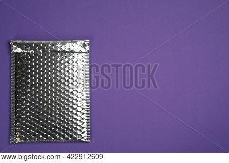 Padded Envelope With Bubble Wrap On Purple Background, Top View. Space For Text
