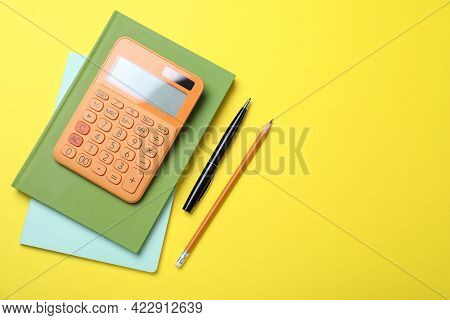 Calculator, Notebooks, Pen And Pencil On Yellow Background, Flat Lay. Space For Text