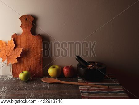 Apples, Maple Leaf, Kitchen Board, Wooden Spoon, Stone Mortar On Wooden Vintage Table. Autumn Fall A