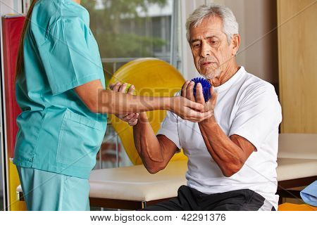 Senior man with spikey balls in gym with physiotherapist