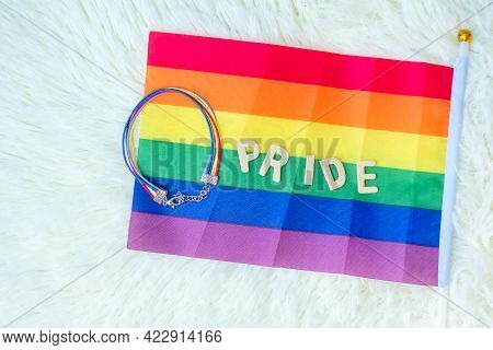 Lgbtq, Rainbow Flag And Wristband On White Background. Support Lesbian, Gay, Bisexual, Transgender A