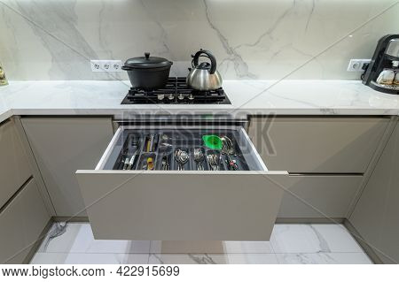 Closeup high angle inside view to open drawer with cutlery at modern grey woden kitchen in classic style
