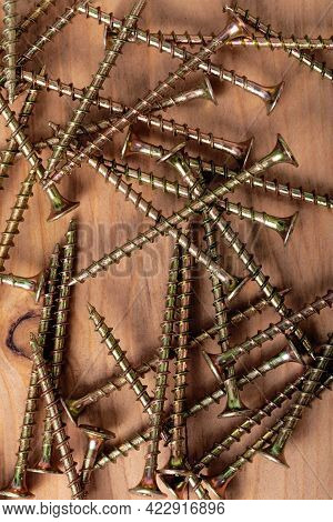 Several Yellow Screws Of Medium Length Lie On Wooden Surface