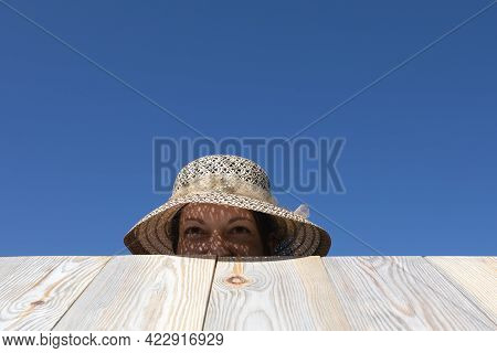 Happy Woman Sticking Out From Behind Wooden Fence Or Table. Game Of Hide-and-seek Or Watching What H