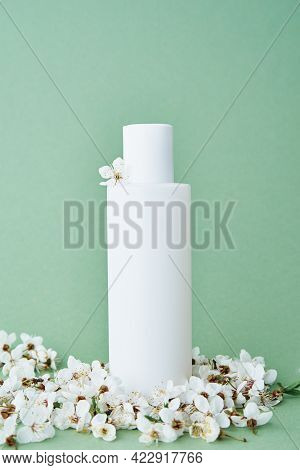Beaty Product Package. Cosmetic Bottle On Pastel Green Background With Blooming Tree Branch. Cosmeti