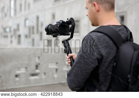 Back View Of Professional Videographer Holding Dslr Camera On 3-axis Gimbal Over Grey Concrete Build