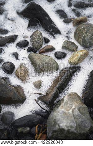 Foamy wave on a rocky shore at Isle of Skye, Scotland