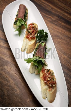 Mixed Tapas Plate With Tomato Bruschetta And Serrano Cured Ham On Wood Table