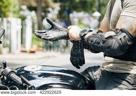 Hands Of Motorcyclist Sitting On Bike And Putting On Riding Gear Like Forearm Guard Pads And Leather