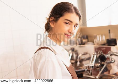 Beautiful Caucasian Barista Woman Looks At Right Side While Making Black Coffee For Customer At Coff
