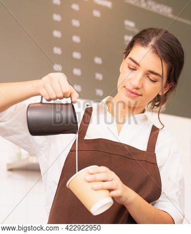 Half-body Angle Of Beautiful Caucasian Barista Women Fills White Milk Into Takeaway Hot Coffee Cup A