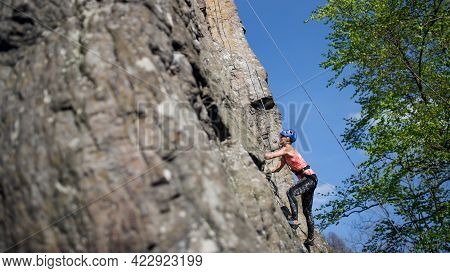 Mid Adult Woman Climbing Rocks Outdoors In Nature, Active Lifestyle.