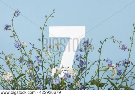 Number Seven Among Blue Flowers On Blue Background. Birthday, Anniversary, Jubilee Concept. For Invi