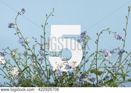 Number Five Among Blue Flowers On Blue Background. Birthday, Anniversary, Jubilee Concept. For Invit