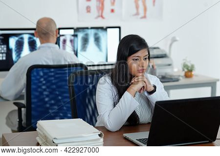 Pensive Young Female General Practitioner Working On Computer And Decoding Medical Tests Of Patient