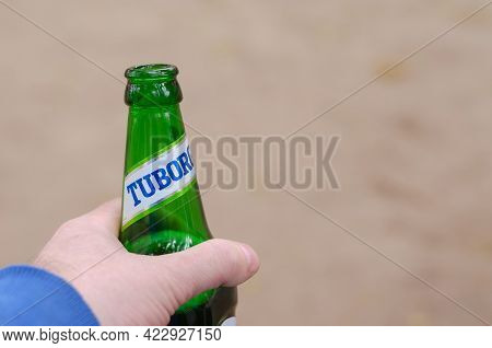 A Man Drinks Beer Tuborg Green. The Hand Holds The Glass Beer Bottle Of The Famous Lager Beer. First