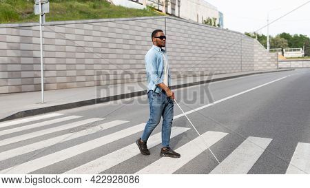 Young Black Visually Impaired Man Wearing Dark Glasses, Walking Across City Street, Using Cane