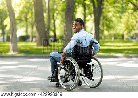 Joyful Handicapped Black Man In Wheelchair Spending Time At City Park, Full Length