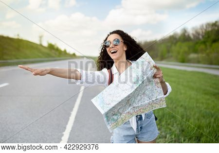 Young Female Tourist With Map Catching Ride, Stopping Vehicle, Hitchhiking On Roadside, Having Autos