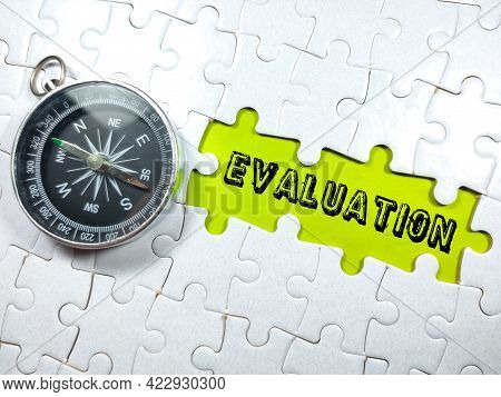 Selective Focus.text Evaluation With Compass And Jigsaw Puzzle On Green Background.