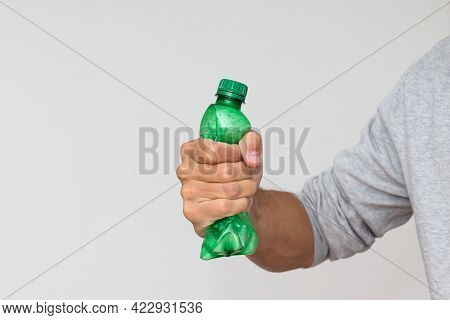 Plastic Bottle Recycling Or Pollution Concept. Hand Squeezing Or Crushing A Green Plastic Bottle On