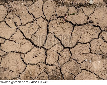 Dry Cracked Clay Soil On The Ground In The Summer During The Heat. Textured, Abstract And Geometrica