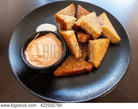 Pieces Of Garlic Bread Or Toasts With Pink Sauce On Dark Plate On Dark Table. Antipasto (appetizer)