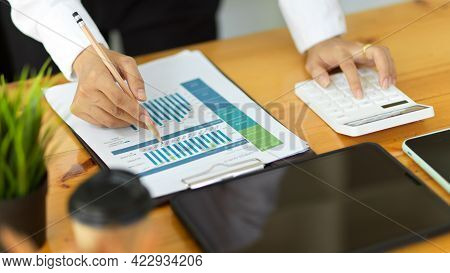 Businessperson Hands Working With Paperwork And Calculator On Workspace