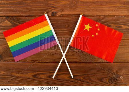 Rainbow Flag Lgbt And Flag Of China On Brown Wood Planks Background. Lgbt Pride Month. Lgbtq. Lgbtqi
